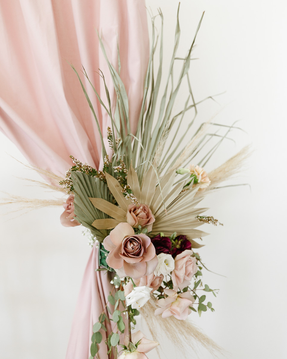A bouquet of flowers attached to a mauve back drop at a party filled with mauve roses, pampas grasses and palm leaves.