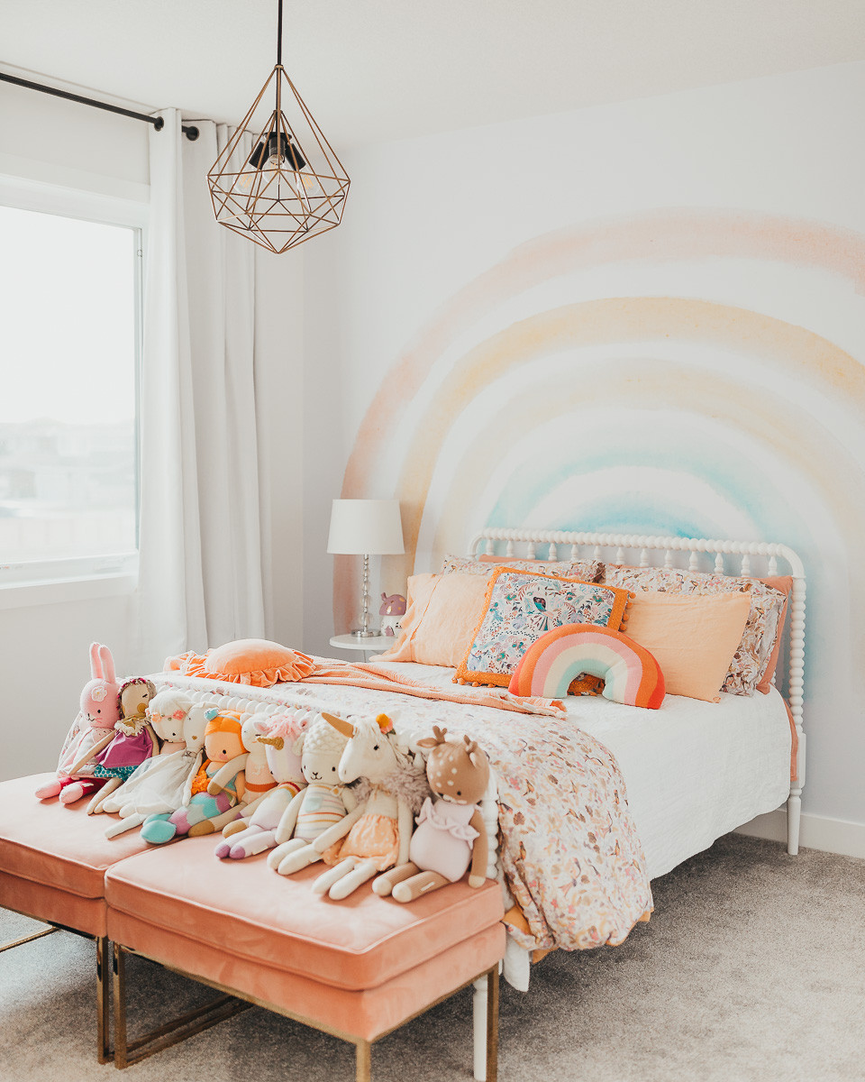 A well styled rainbow themed little girls bedroom decorated with soft rainbow colors and floral bedding on a Jenny Lind bed frame with a rainbow wallpaper on the wall..