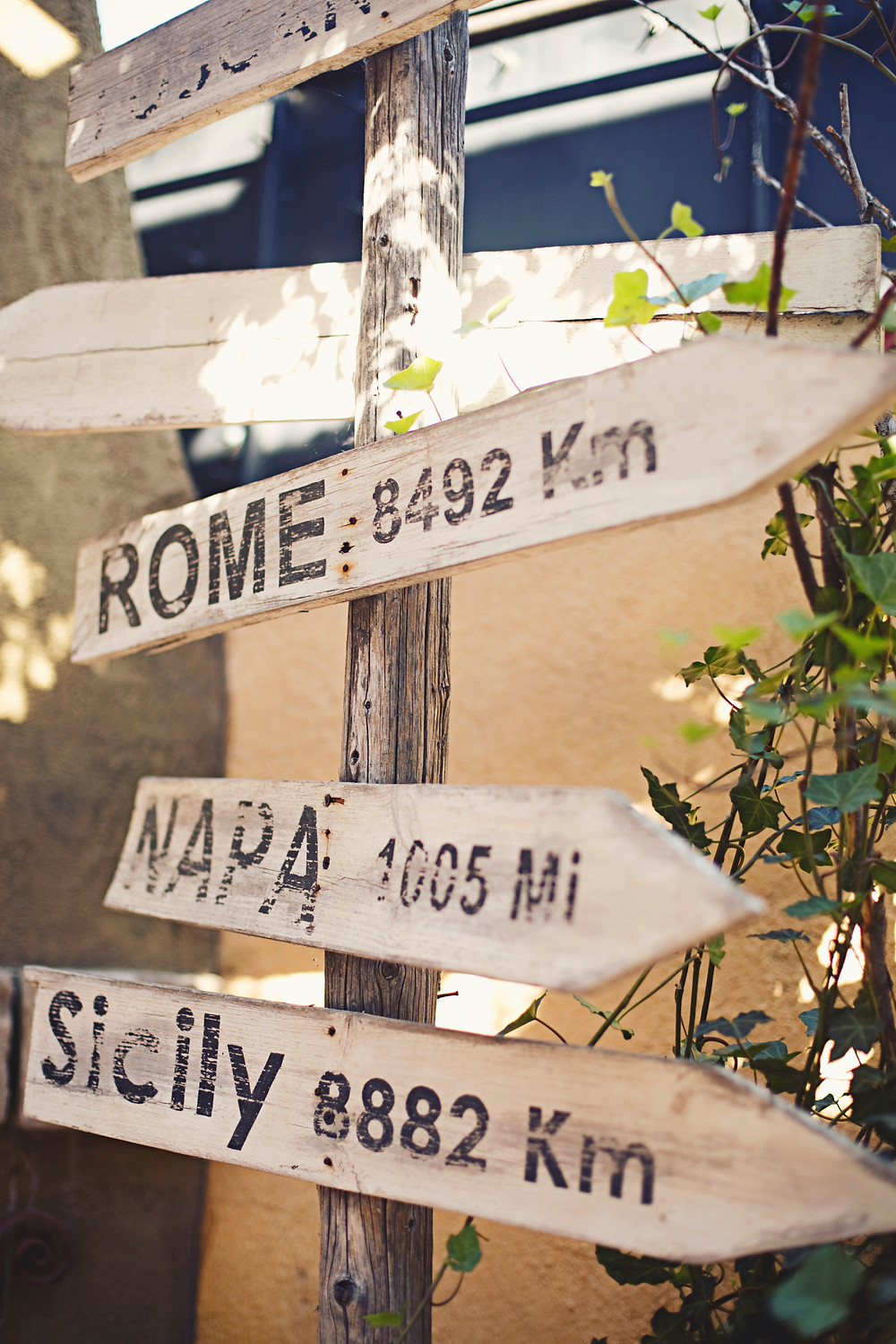 Some wooden signs at a rustic Italian inspired wedding with Italian city names written on them.