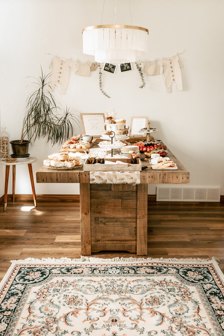 A large rustic wooden table at a boho baby shower displays a collection of appetizers and beautiful desserts beneath a white chandelier.