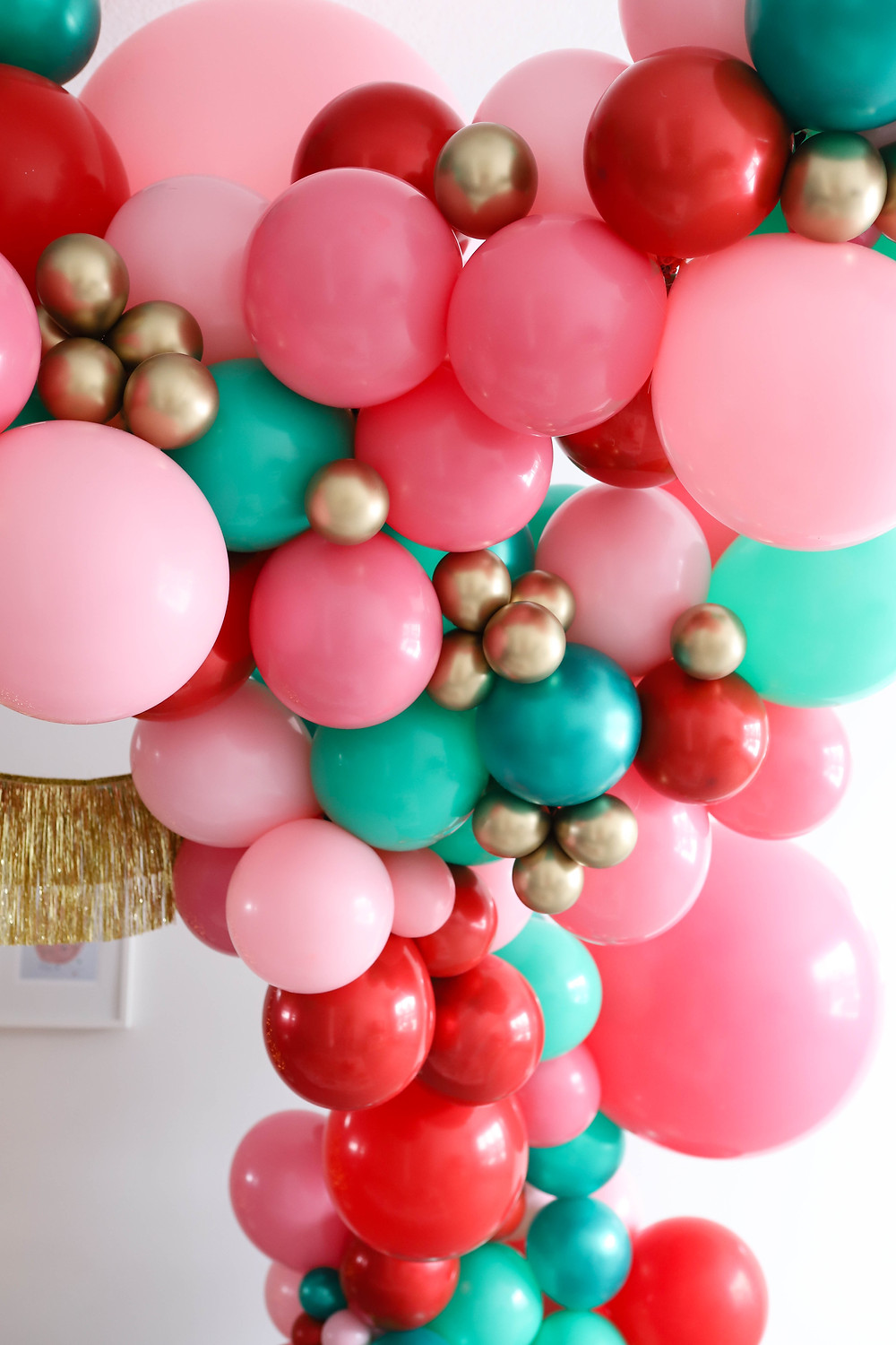 A holiday ballon garland set up at a kids christmas party in mint, pink and red colors with gold fringe accents.