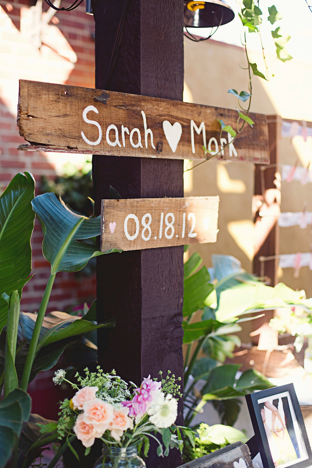 A wooden post displaying some wooden signs at a rustic Italian wedding.