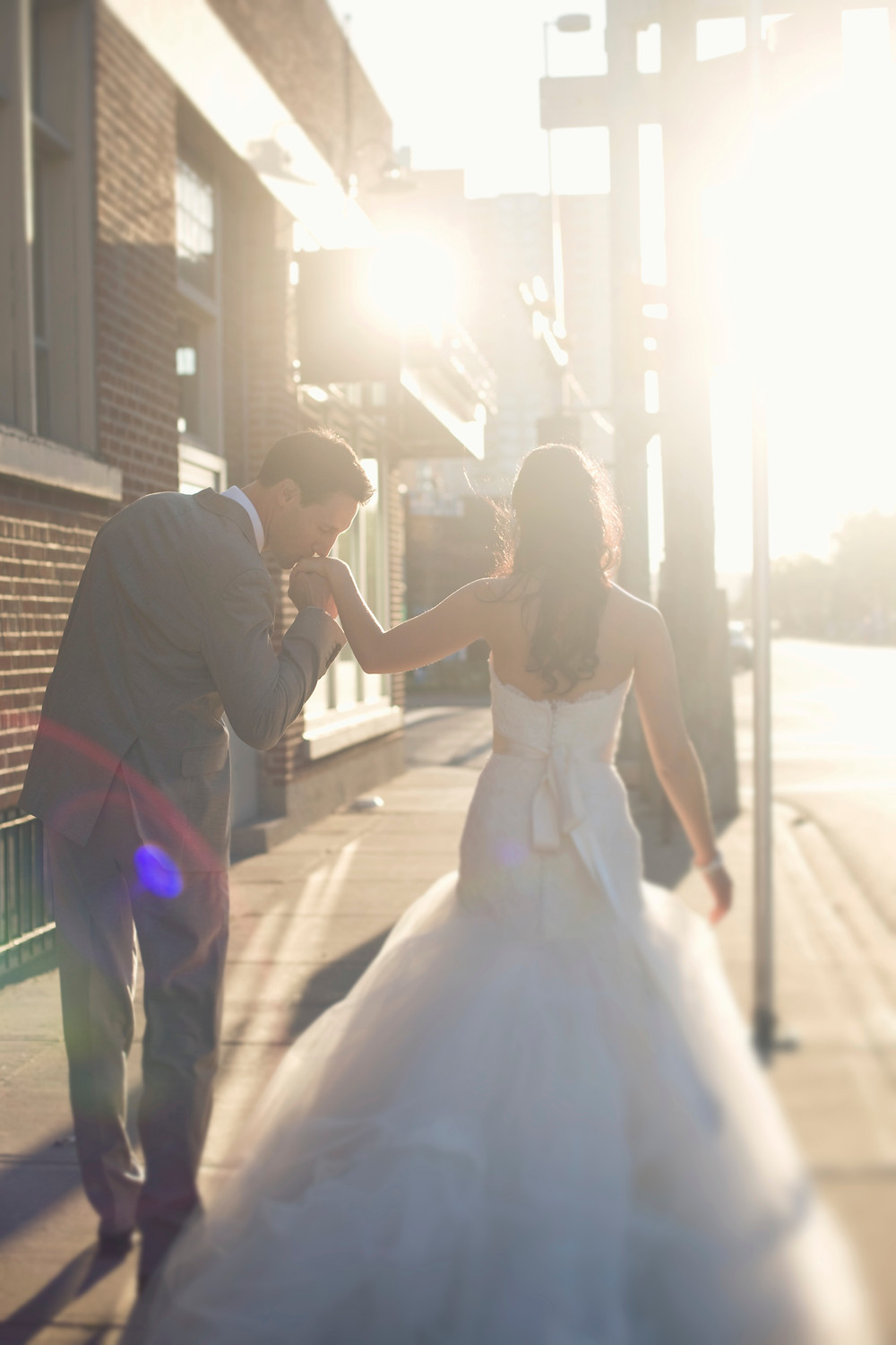 A bride and groom walk off into the sunset on their wedding day hand in hand.