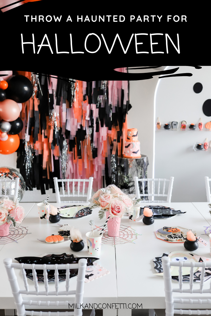 A wall filled with black, orange, pink, sparkly arched streamers for a children's halloween party filled with decorations on a white kids table with black bat plates and cups with black and white straws, next to pink roses and pumpkin cookies.