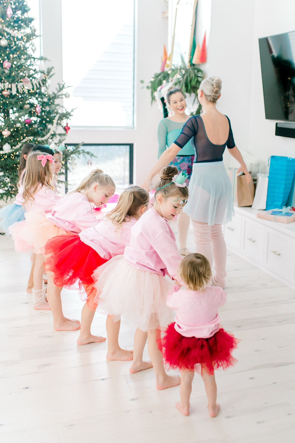 A group of girls at a birthday party are dressed in white, red, and pink tutus with pink sweaters dance with two adult ballerinas.