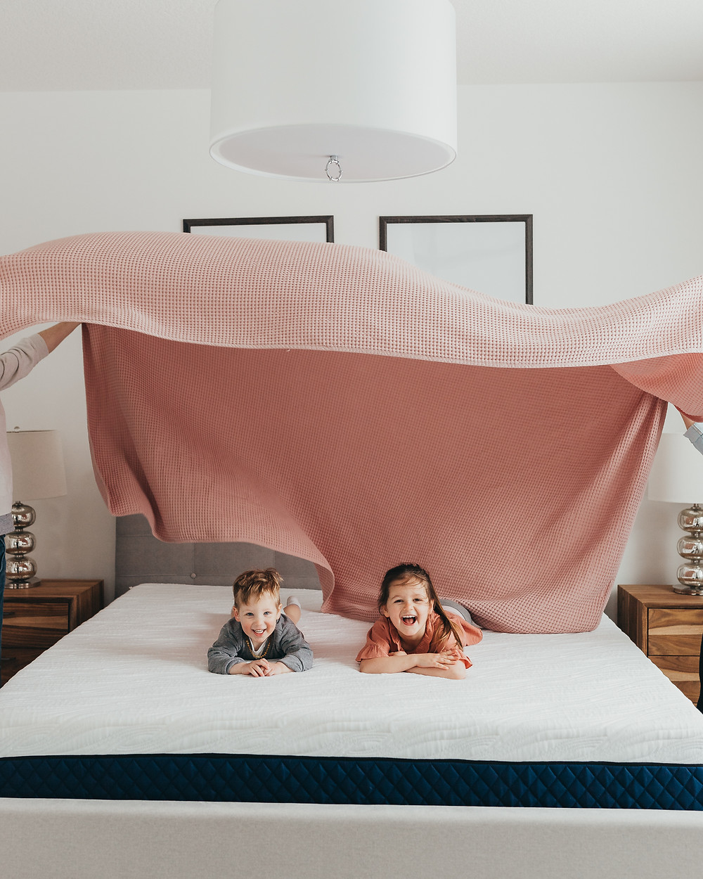 A little girl and boy playing on the bed as a pink sheet is fanned above them.