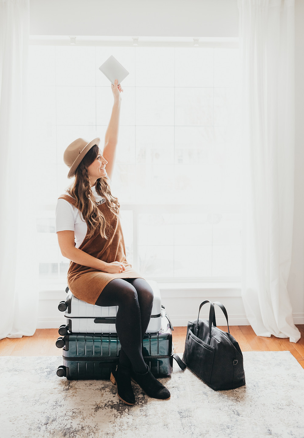 A girl sitting on some stacked luggage holding up a passport excited about her travels.