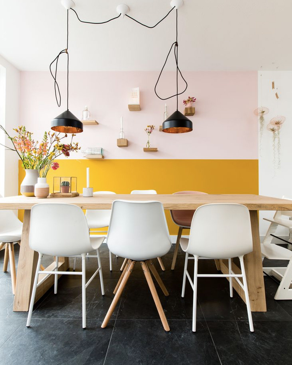 Half yellow wall in kitchen with black and gold pendant lights over wooden table white plastic chairs white high chair wooden floating shelves black floor vases with flowers cactus and single white candle holder
