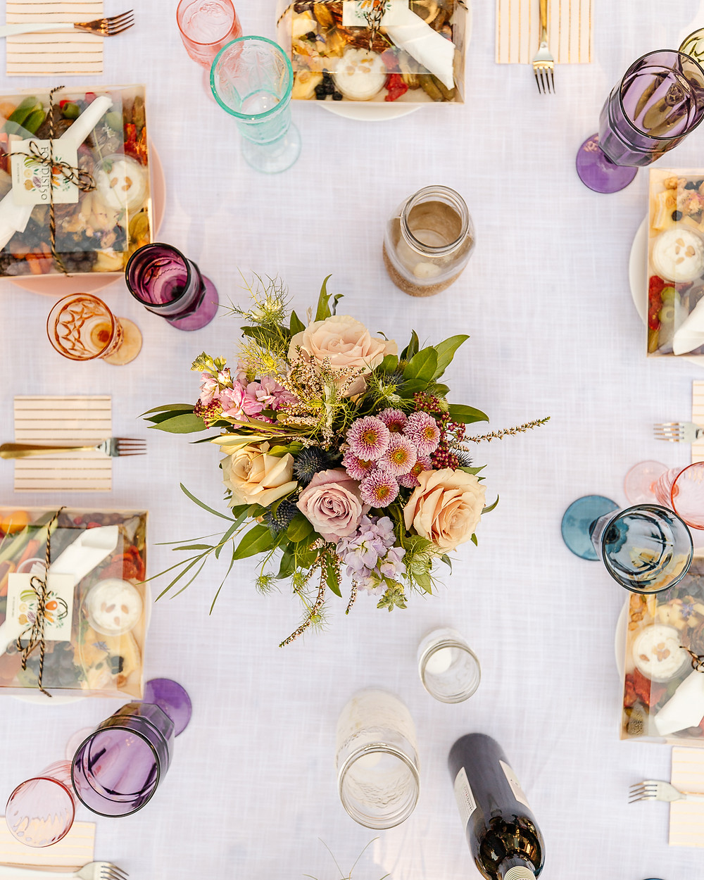 An evening backyard boho garden party with gorgeous flowers, vintage rugs, charcuterie wine, twinkle lights, coloured glasses, table decor, boho decor and all your best girlfriends.