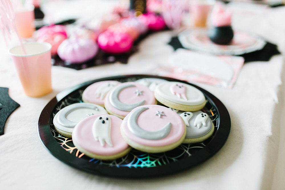 A plate of pastel Halloween cookies at a kids Halloween party done with black, pink, purple and orange colors.