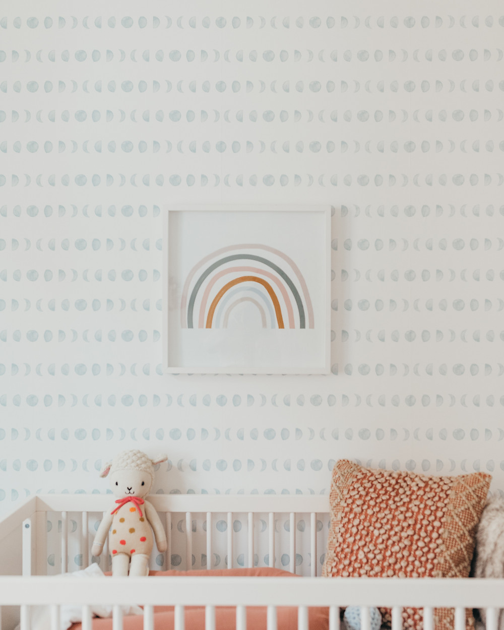 A framed rainbow print hanging above the crib in a nursery.