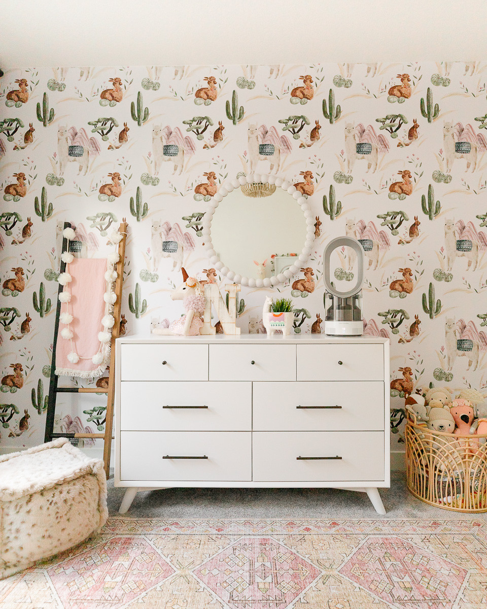 A nursery with a midcentury modern white dresser with black handles, a wooden blanket ladder and a round mirror in front of a wall covered with feminine llama and cactus wallpaper.