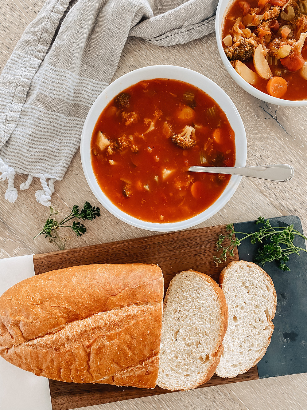 Two bowls of hearty vegetable soup sit on the table surrounded by a grey tea towel, sliced bread and fresh herbs.