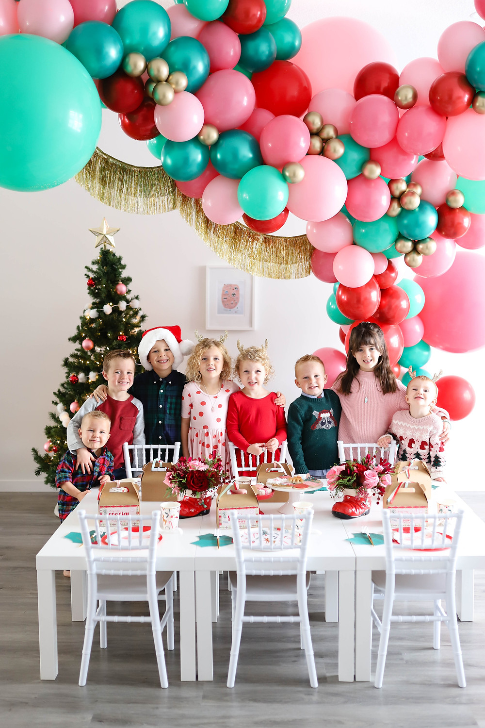 A kids christmas holiday party planned with balloons, gingerbread house and cookie decorating, DIY decor and magical printables.