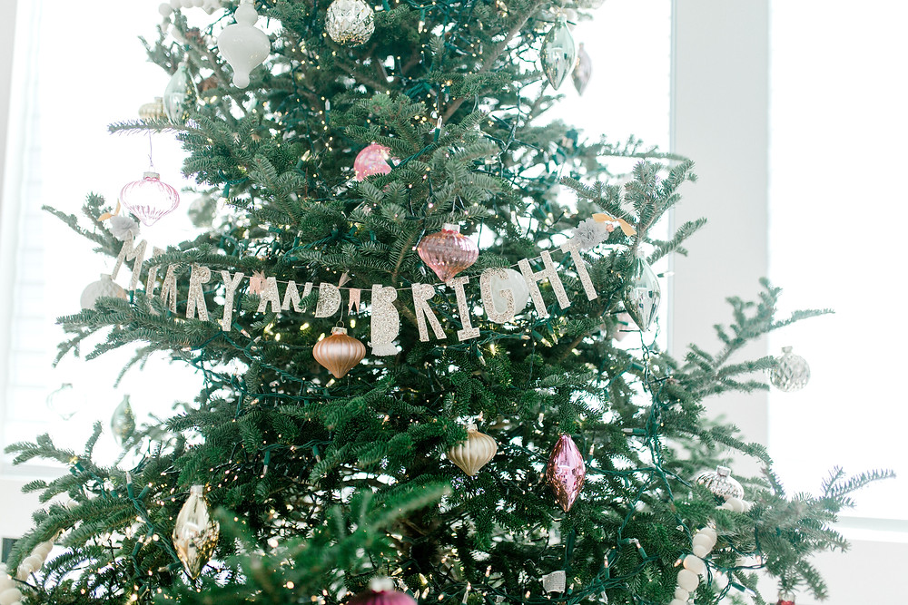 Christmas tree decorated with lights, metallic and pink ornaments and a 'merry and bright' garland.
