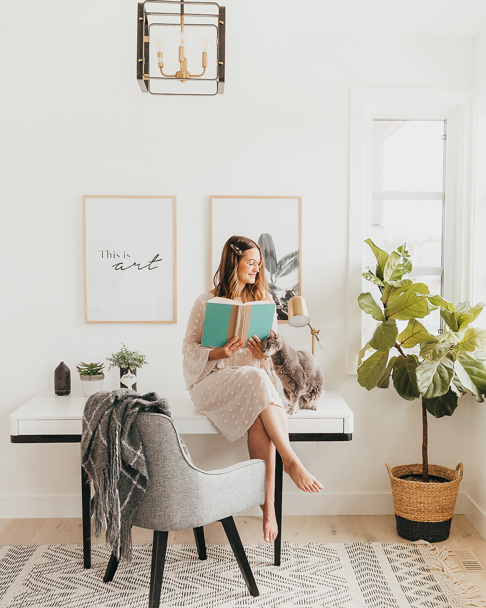 A woman in a boho white dress sits with her grey cat on a modern white desk in a home office with a grey chair and ivory boho rug next to a fiddle leaf fig plant and some modern art prints.