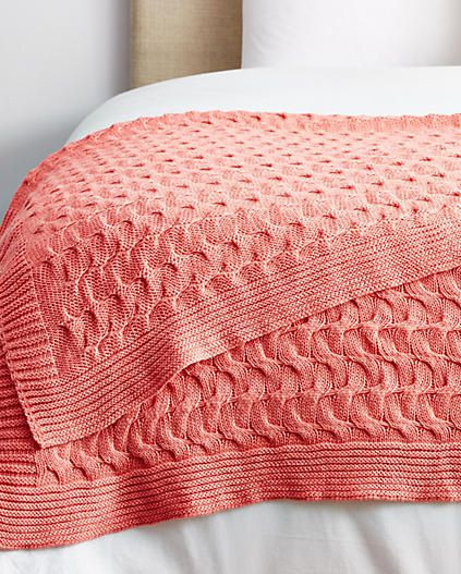 Cotton coral throw blanket on the bed