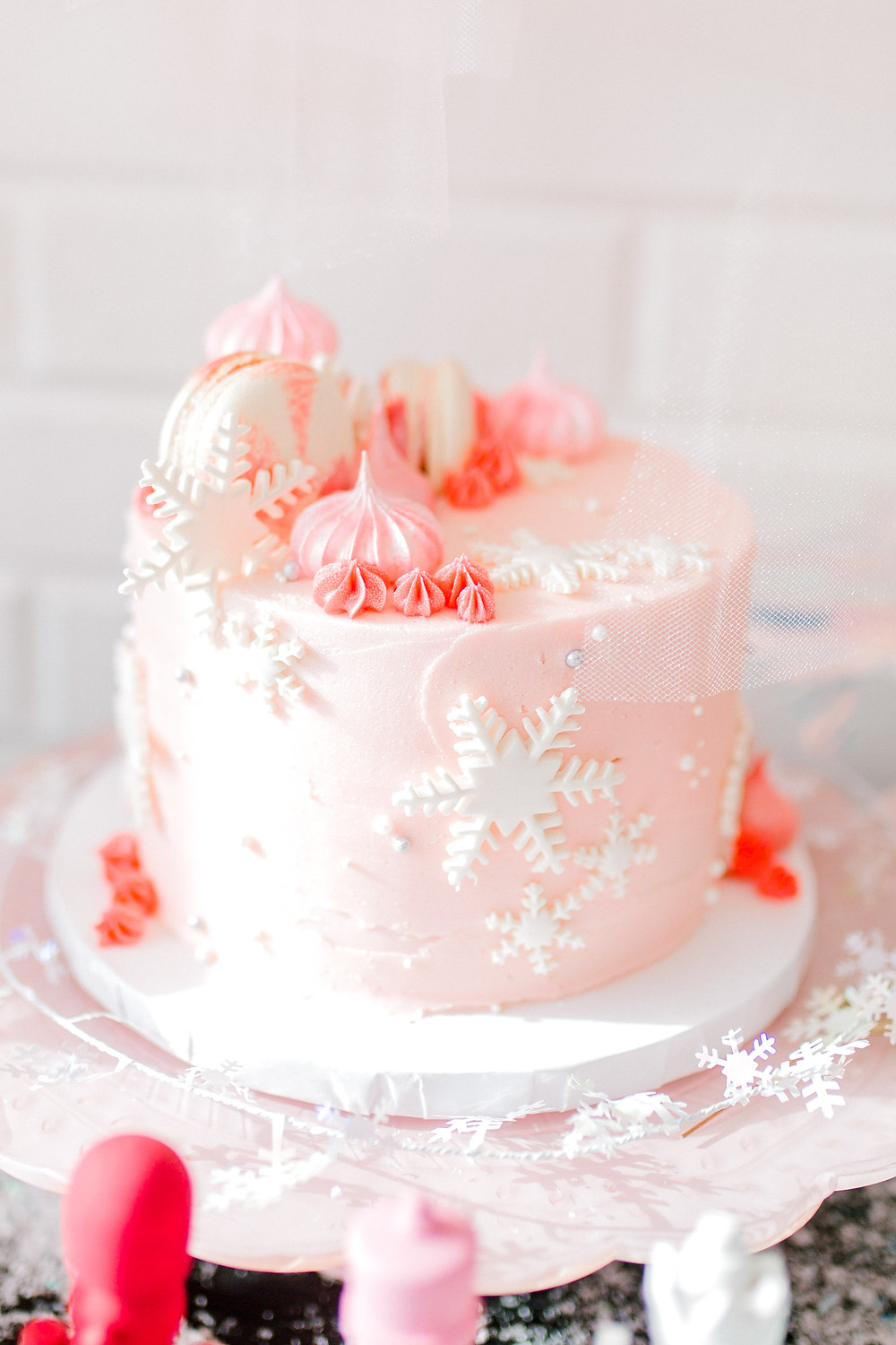 A pink nutcracker birthday cake with white snowflakes, white macarons, pink icing with beads on a white platter.