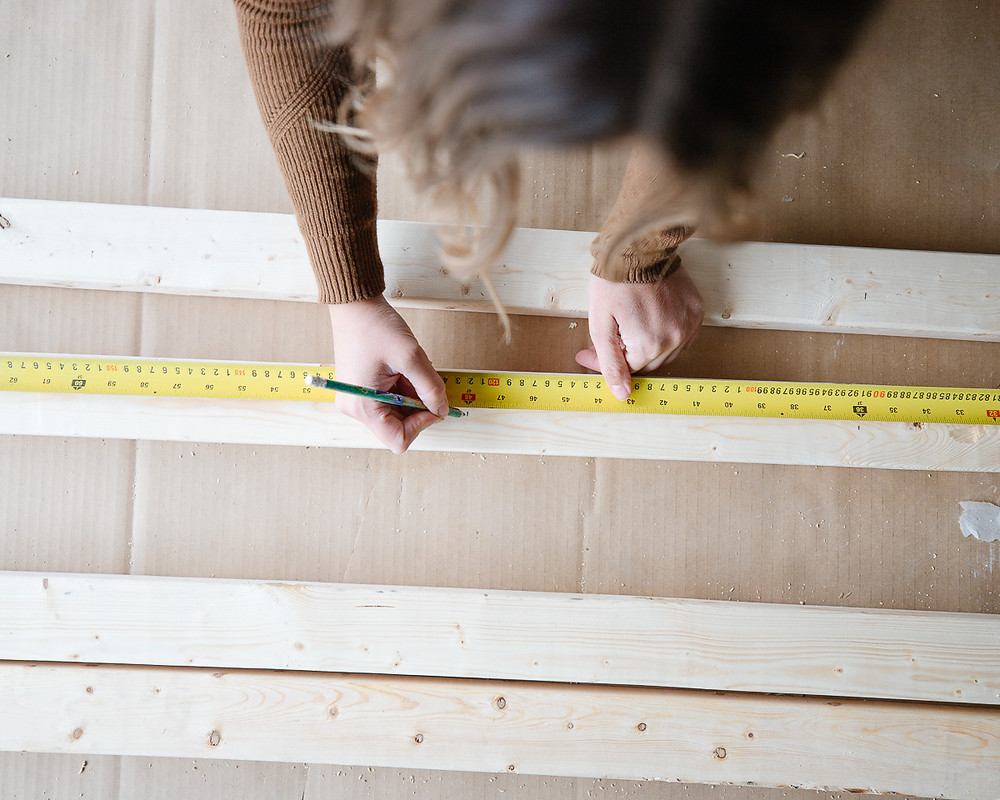 A girl marking out measurements on a piece of wood.