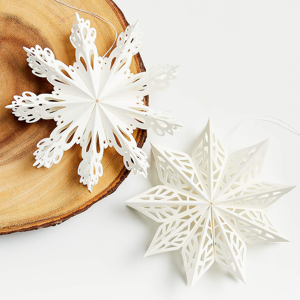 Two white paper snowflakes sit on a wooden stump for a Scandinavian Christmas.