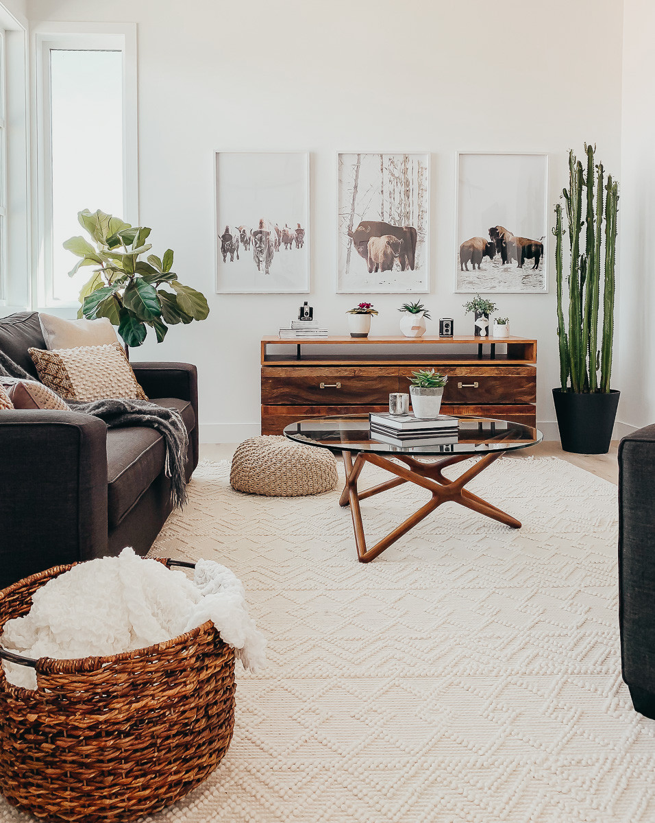 A basket of blankets sitting in a midcentury modern living room.