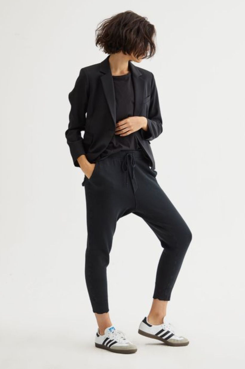 Woman with cropped bob haircut standing against a white wall wearing a black blazer with black joggers and white striped sneakers