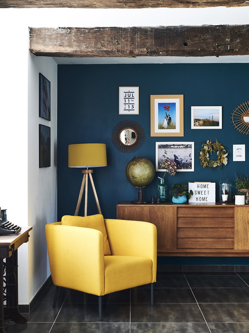Yellow floor lamp yellow accent chair mid century sideboard typewriter gallery wall globe home sweet home sign with vases and plants blue background wall