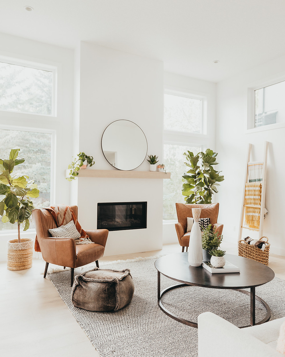 A white walled living room features natural light wood floors with a natural fibre striped rug, metal round coffee table, two brown leather chairs, brown fur pouf, blanket ladder, two fiddle leaf fig plants and a fireplace with a natural wood mantel holding a mirror and some plants.