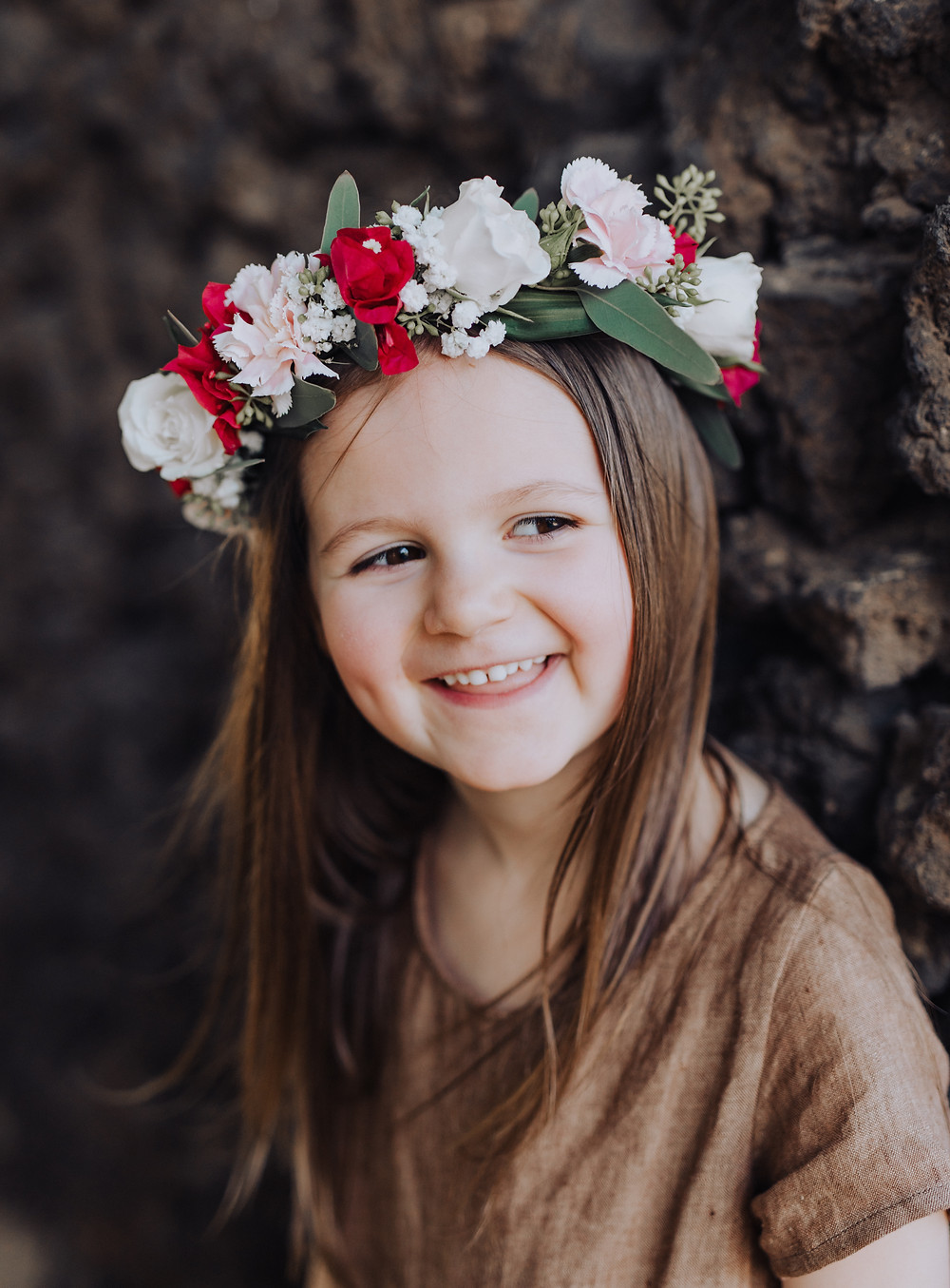 A little girl is smiling wearing a flower crown in her hair.