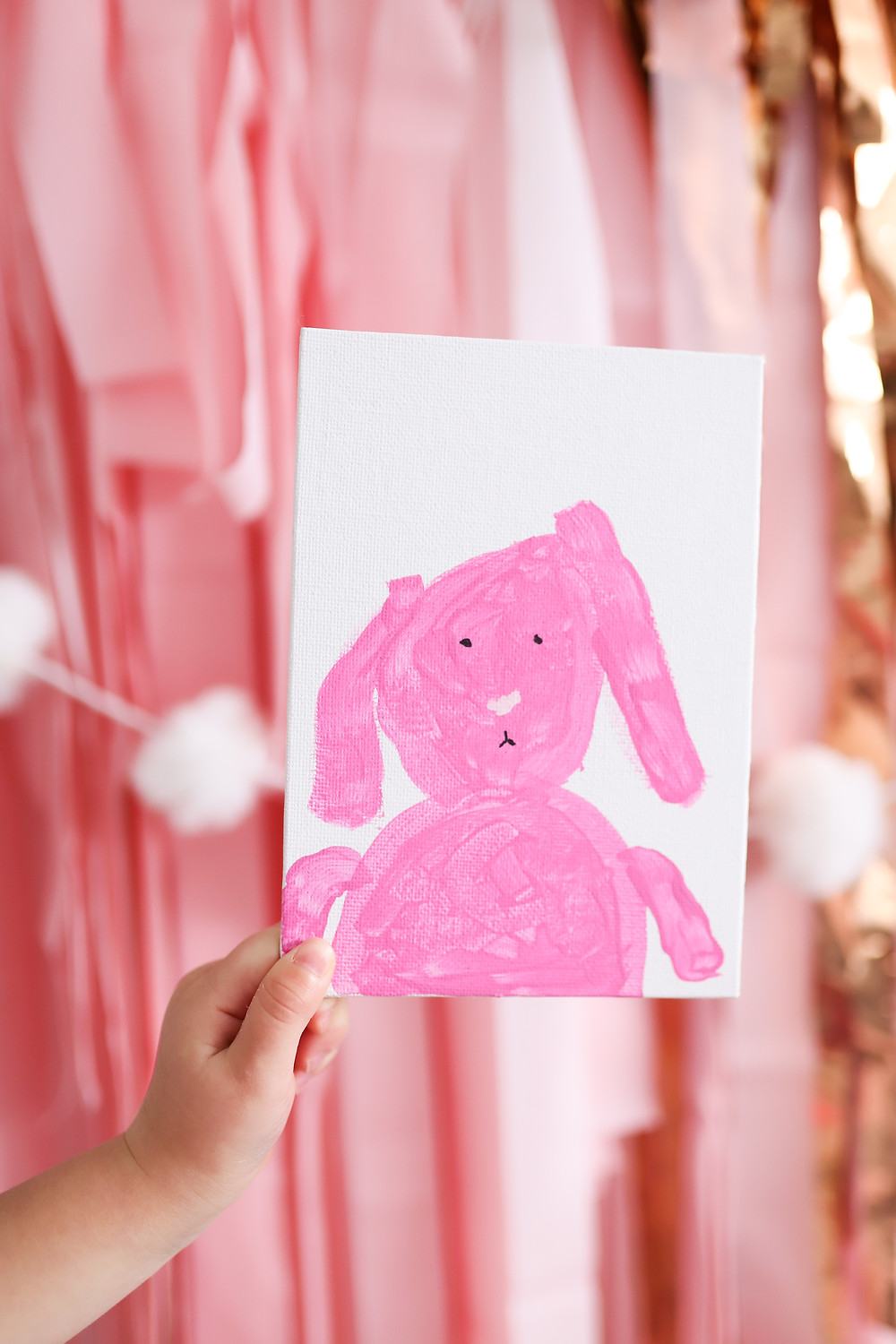 A pink bunny drawing painted on a piece of paper made by a child.