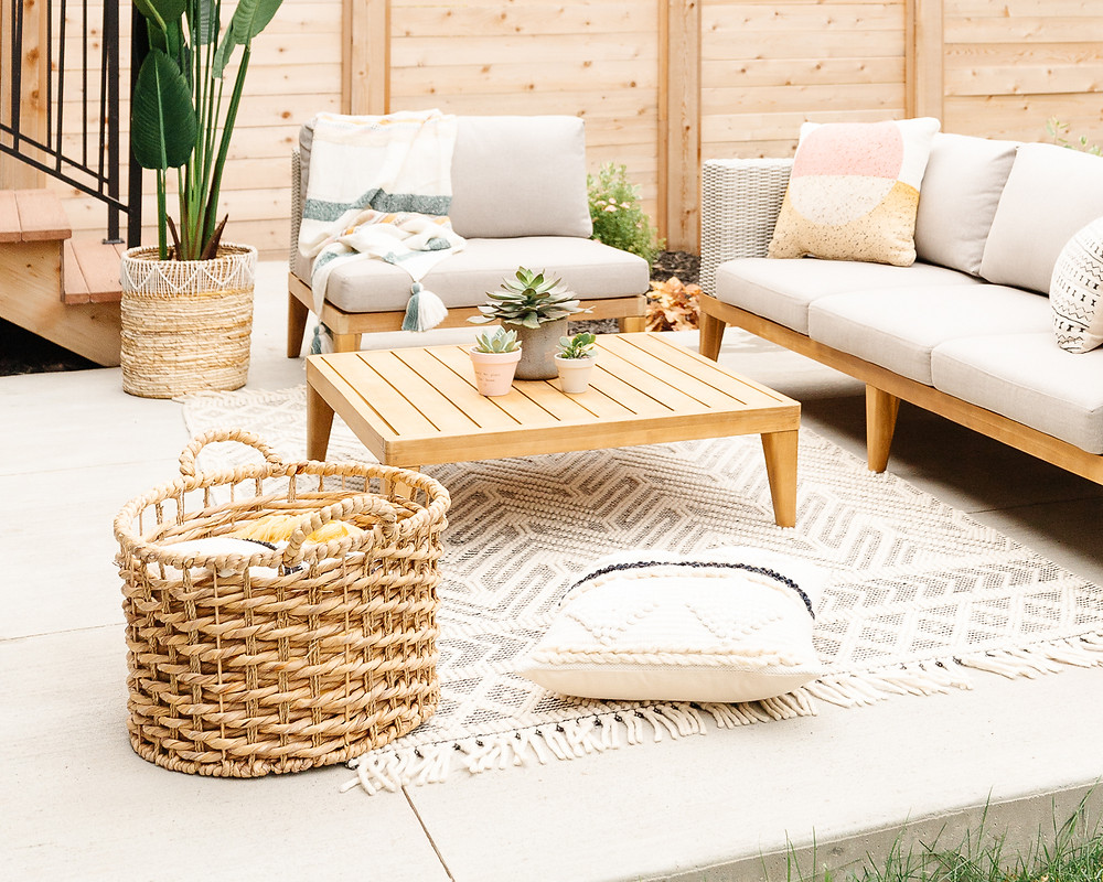 Modern wicker sofa with wood accents and beige cushions black and white area rug chair with wood accent and striped throw blanket wood accent table with succulent pots wicker basket with blankets patterned oversized pillow on rug potted plant wood fence backyard concrete patio space
