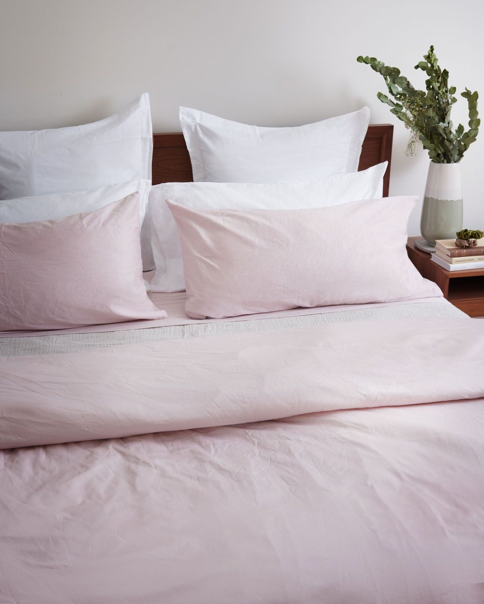 A blush pink duvet and pillow cases on a modern bed.