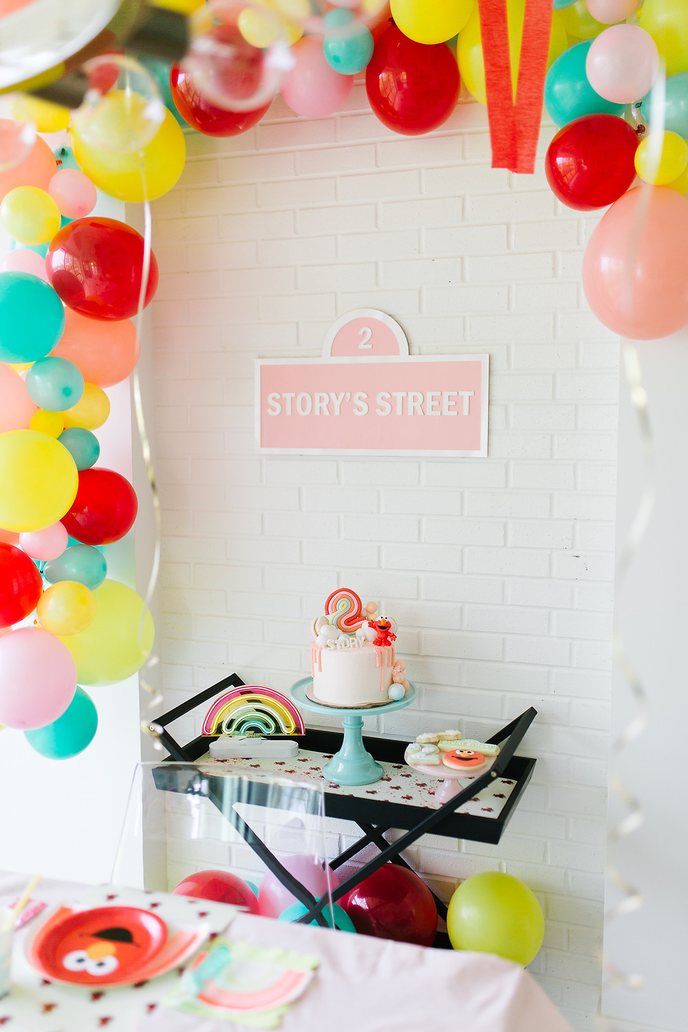 A Sesame Street Elmo birthday party with colourful balloons, pink Elmo birthday cake, Elmo cookies, rainbows, Elmo plates and pink signage.