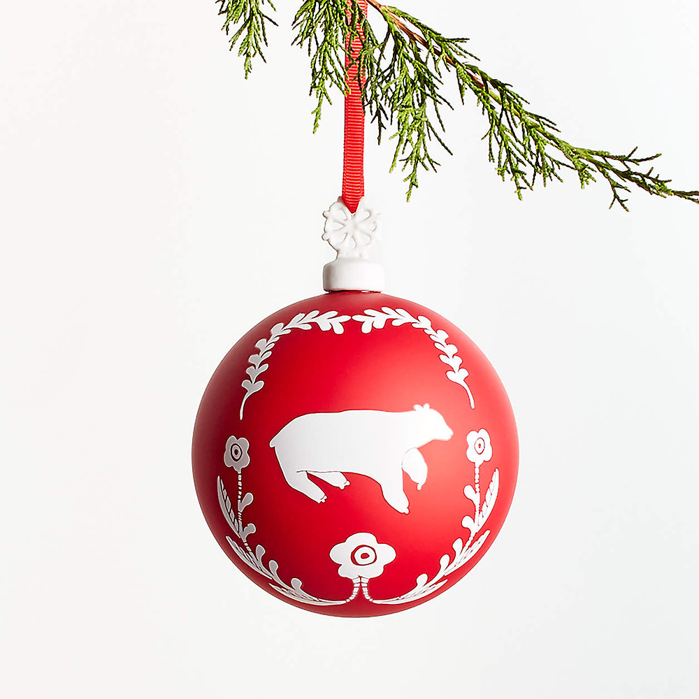 A red and white Scandinavian nordic inspired ornament hangs from a green tree branch for the Christmas holidays.