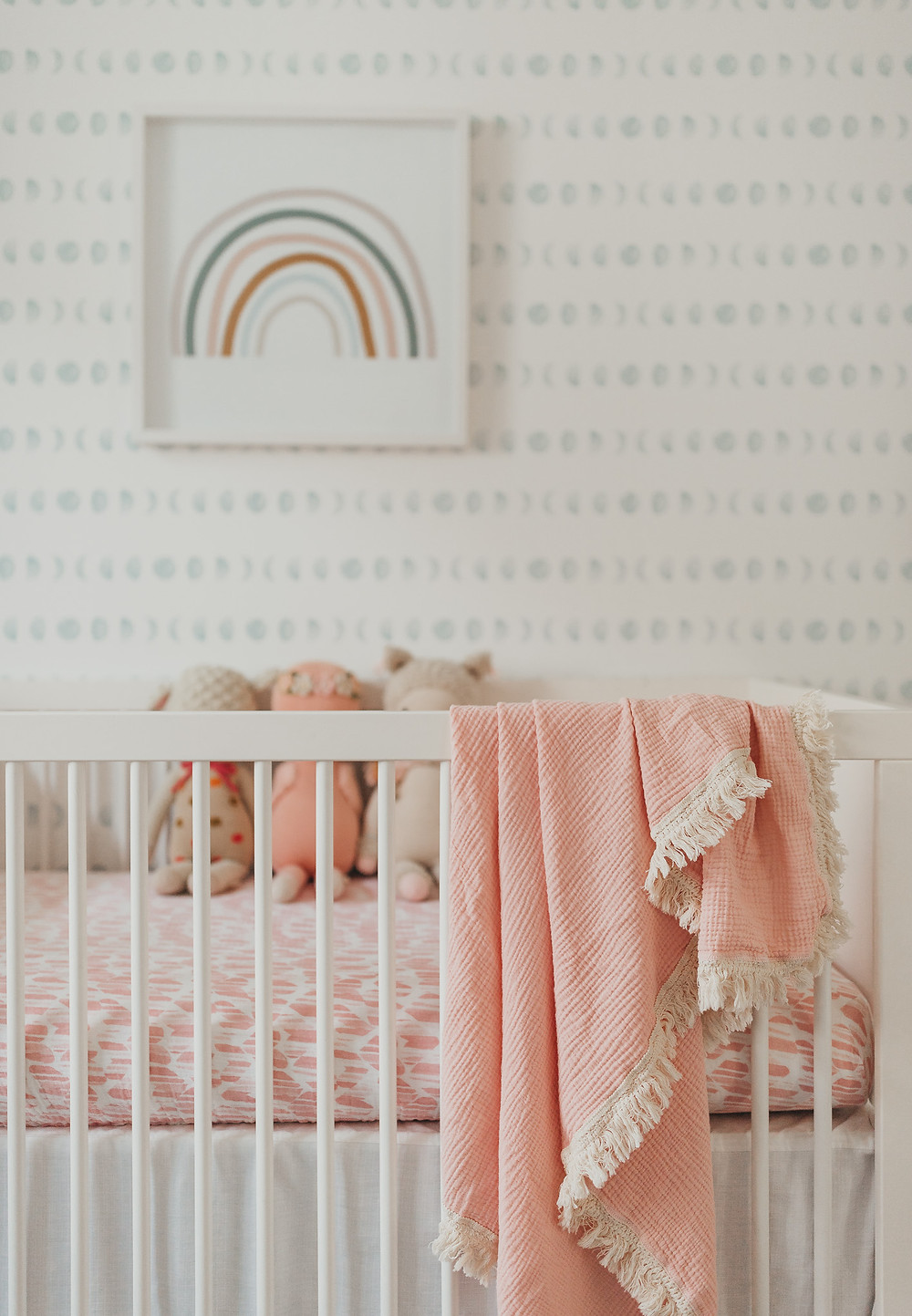 A peachy blanket hanging over the edge of a crib.