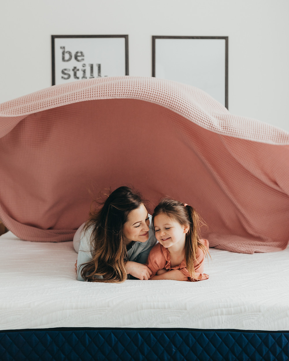 A mother and daughter cuddling on the bed together under a pink blanket on their silk and snow mattress.