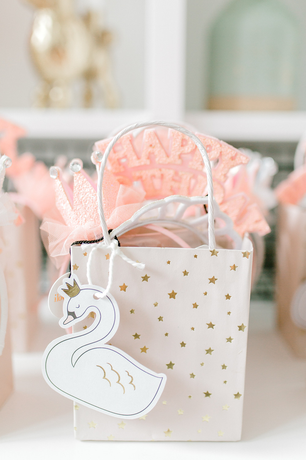 A white gift bag with gold stars, pink tulle, white crown and a white swan attached to it at a nutcracker party.
