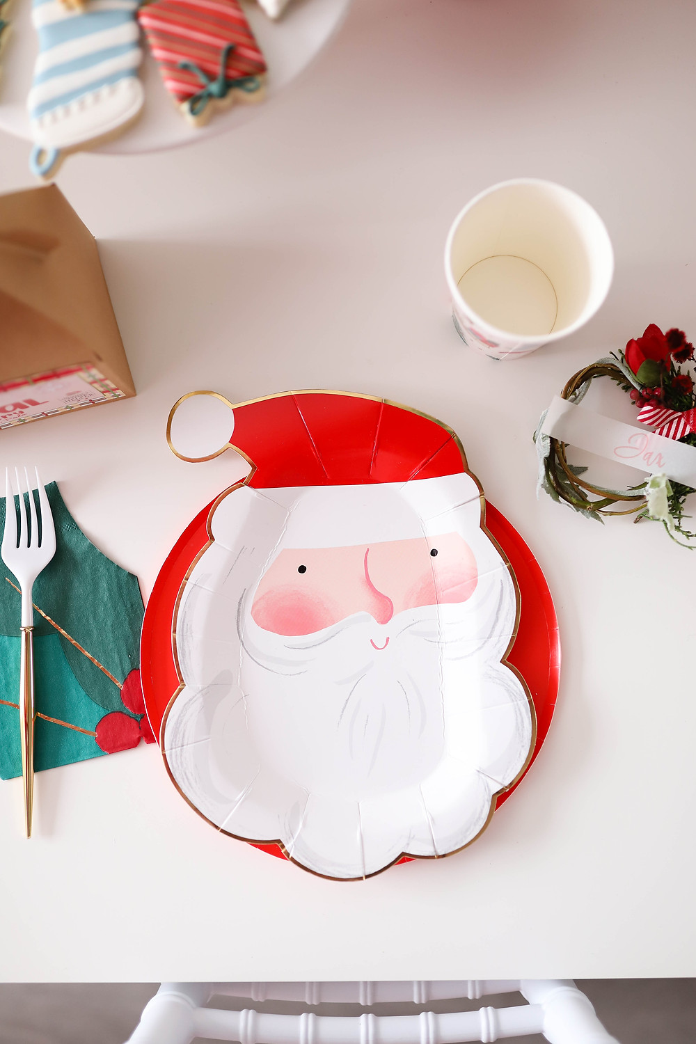 A Santa paper plate on a white table for a kids Christmas party next to a mistletoe napkin.