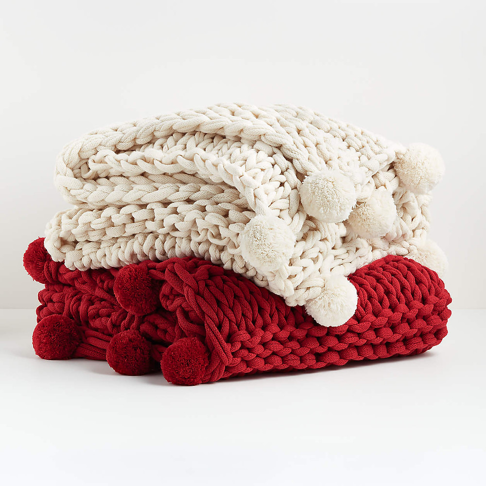 A cream and red chunky knit blanket with pom pom tassels that is perfect for the Christmas holidays.