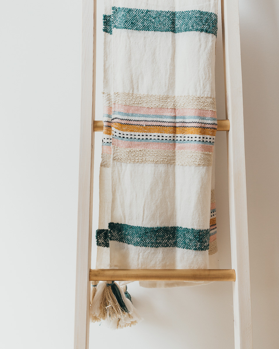 A striped boho throw blanket hanging over a gold and white blanket ladder.