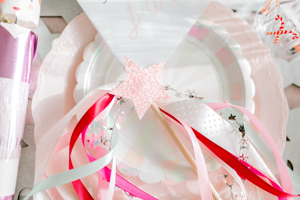 A table setting with white snowflakes, pink plates, pink and white utensils, a pink nutcrackers and a sugarplum fairy wand at a party.
