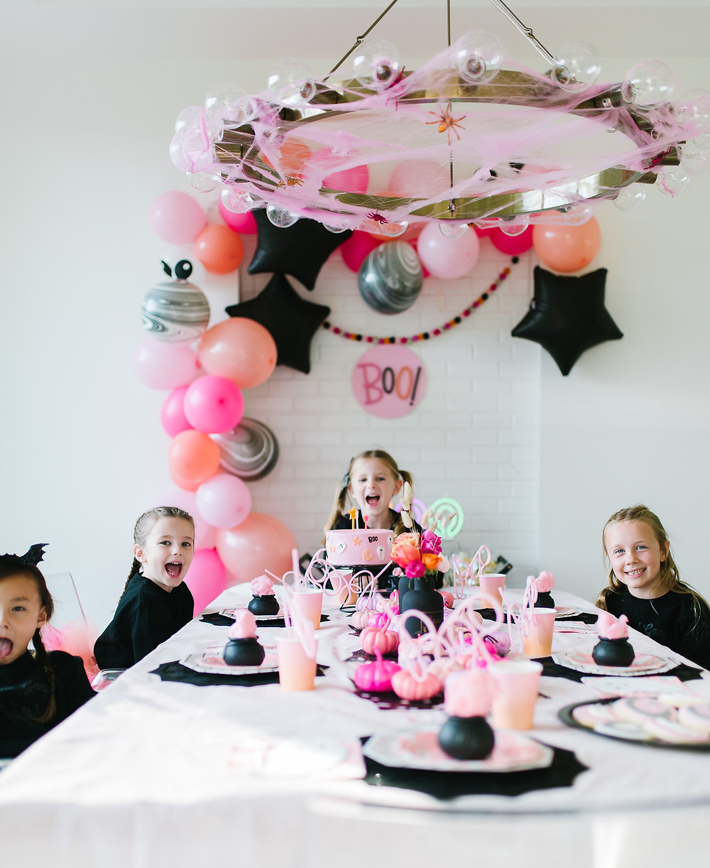 Ghoul gang halloween party with a tablescape of Halloween decor including painted pumpkins, balloons and flowers.