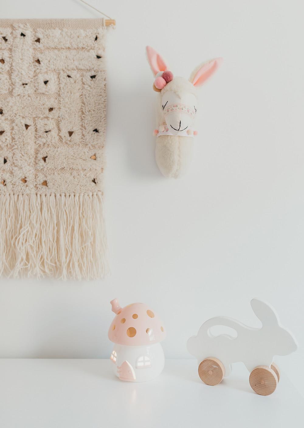 A faux llama head hanging in a baby nursery.