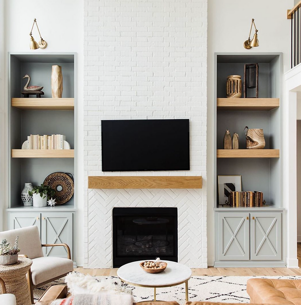 A stunning white brick fireplace with a wood mantle in the centre of two dusty grey blue bookshelves with wood shelves styled with decorative accessories and books.