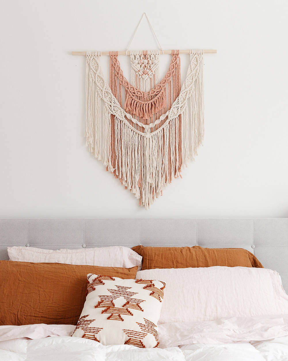 Macrame wall hanging natural wood with cream and blush accents above bed with grey headboard and rust and white pillowcases aztec pattern throw pillow accent