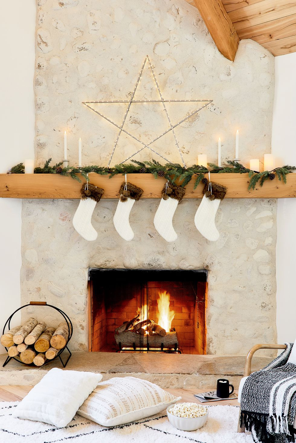 A concrete Christmas holiday fireplace with a mantel decorated with greenery, stockings, candles and a large star with a basket of blankets and a stack of wood on the floor for a modern and cozy feel.