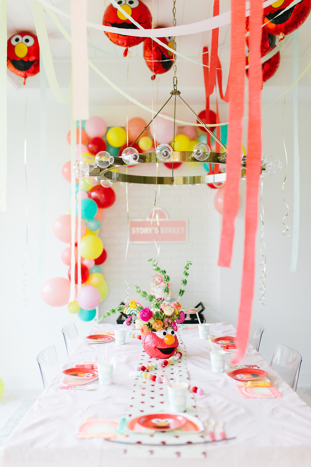 A Sesame Street themed birthday with an Elmo cake and bright coloured decorations hung over a decorated party table.
