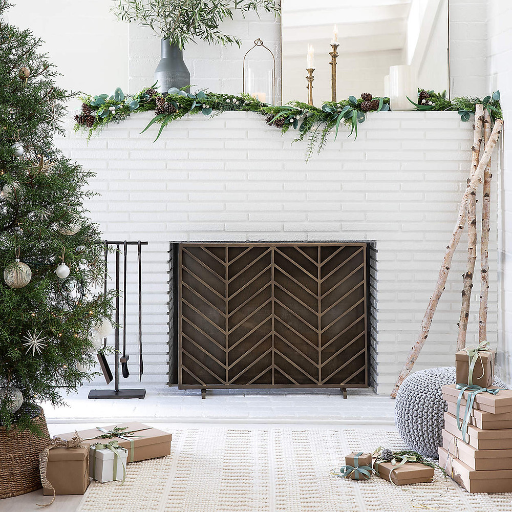A white brick fireplace styled for the Christmas holidays with greenery and candles on the mantel beside a Scandinavian inspired Christmas tree.
