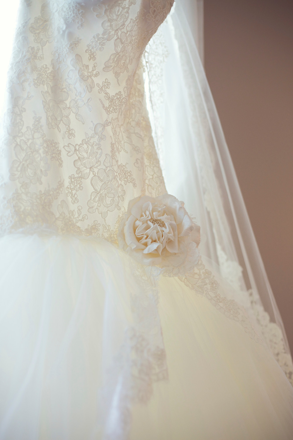 A white Lazaro wedding dress off lace and tulle hanging from a window on the wedding day.