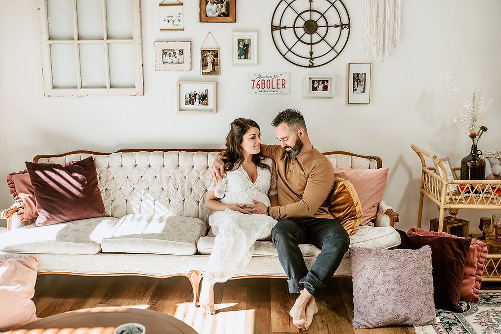 A pregnant couple sits on a white vintage sofa with the wife in a white lace dress and the husband in earth tones as he rests his hand on her belly.